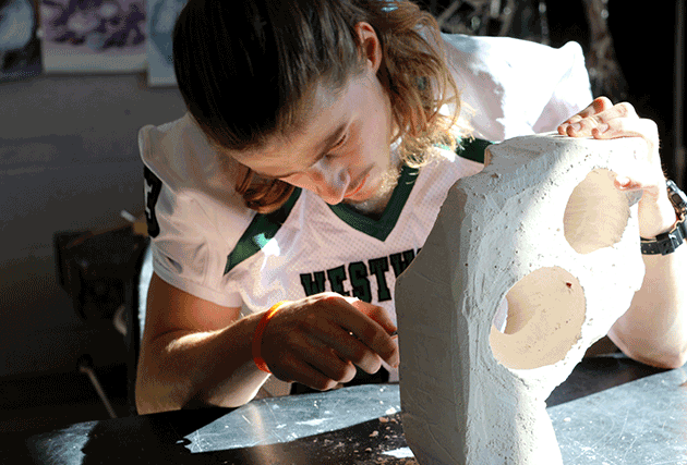 student sculpting stone