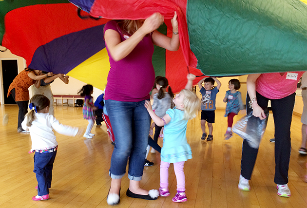 children and adults playing with a parachute
