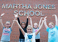 Picture of Students Outside Martha Jones School Sign