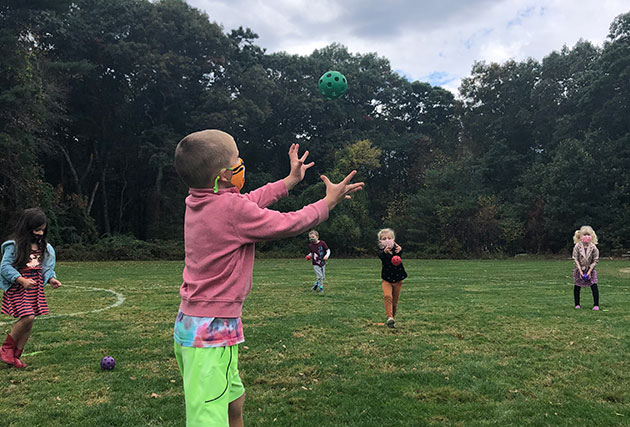 A student reaches to catch a green ball during a recess game.